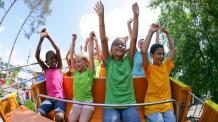 Kids raising hands on roller coaster