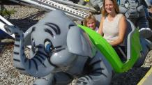 Mom and daughter sitting in flying elephant kiddie ride