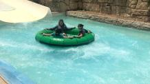 Teens in a green water raft flowing down Texas Tumble