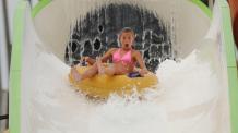 Girl on Big Kahuna water slide at Six Flags New England Hurricane Harbor