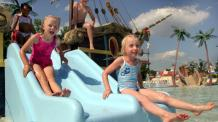 Kids slide down slide of ship in water of Splashwater Spring play area