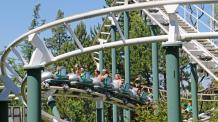 Group of families riding Spacely's Sprocket Rockets green and white track