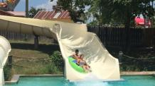 Guests sliding down water slide in green tube