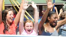 Three female friends with their hands in the air on a spinning thrill ride at The Great Escape.