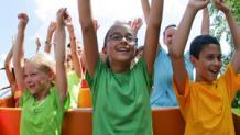 Kids raising hands on roller coaster