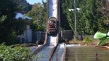 Log ride vehicle splashing down the drop greeted by Yosemite Sam riding a green dragon