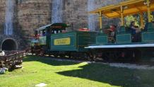 Train carrying guests passing by quarry wall with three waterfalls