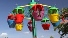 Guests riding inside colorful ride carriages while slowly spinning in the air