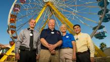 Six Flags employees standing in front of a ferris wheel