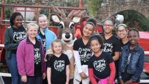 group of girls standing with a reindeer character