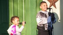 Two children sing karaoke on stage