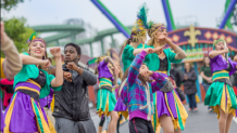 Dancers in Party Gras in front of THE JOKER coaster