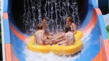 Teens tubing down water slide