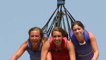 trio of women on Dare Devil Dive lifting into air