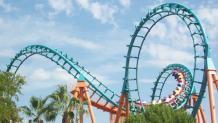 Boomerang coaster vehicle winding through the teal coaster track