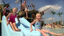 Kids slide down slide of ship in water of Splashwater Spring play area