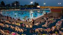 Guests watch a movie on a big screen while lounging in the wave pool