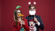 Couple having fun with props while wearing ugly holiday sweaters