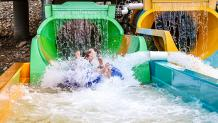 Couple on two person tube splashing out of exit