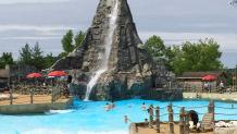 Wide shot of Hurricane Bay wave pool featuring a large volcano with a waterfall