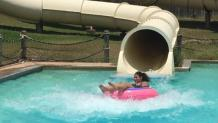 Girl exiting water slide on tube