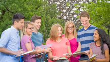 Group of teens holding clipboards in front of Goliath