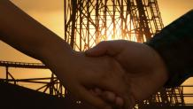 two people holding hands in front of a coaster