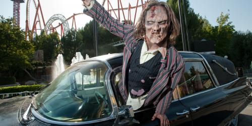 Zombie leaning out the window of a hearse in front of a roller coaster during Fright Fest at Six Flags