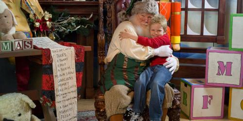 A boy sitting on Santas lap in his workshop during Holiday in the Park at Six Flags New England