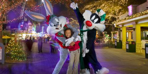 Bugs Bunny and Sylvester pose with a girl in a festive Christmas setting.