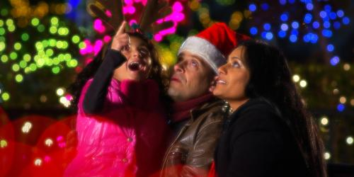 Family of three looking at lights in awe.
