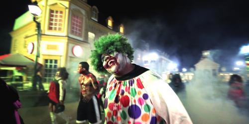 A creepy clown with green hair walking down a fog-filled Main Street