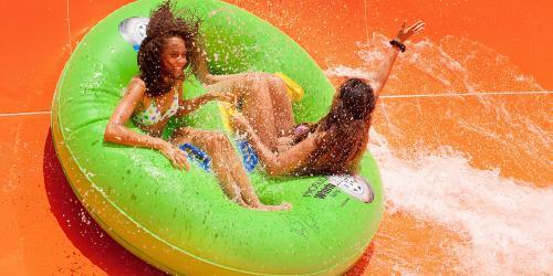 Teens riding water slide