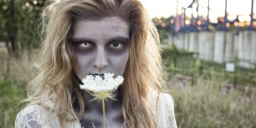 Zombie in white dress holding a flower while in front of a roller coaster