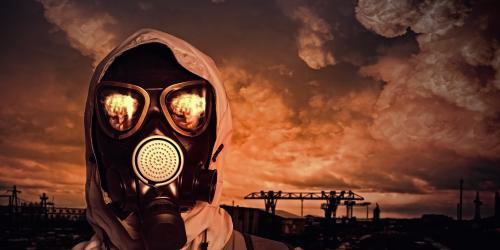 Person with gas mask with orange sky in wake of the Aftermath