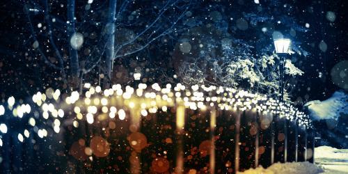 Snowy bridge with warm christmas lighting and a single light post