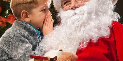 Boy whispering to Santa