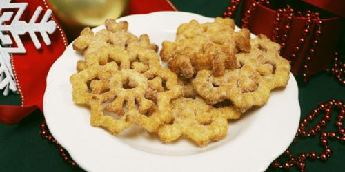 Buñuelos on a plate surrounded by holiday items
