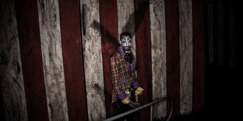 Scary clown against striped backdrop standing alone