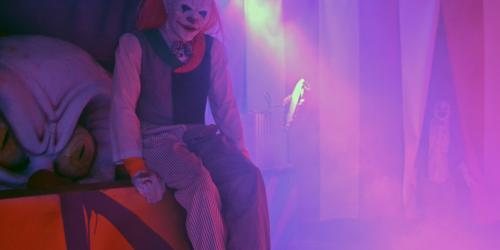 Evil Clown looking at you sitting on giant box with other clowns in background