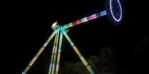 Pendulum swinging ride at night with lights on the ride