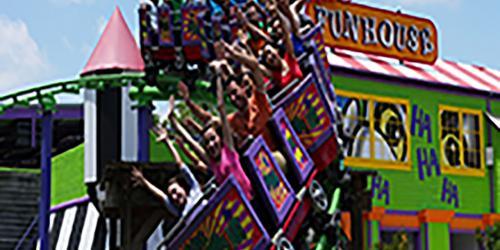 Guests enjoying THE JOKER Funhouse Coaster