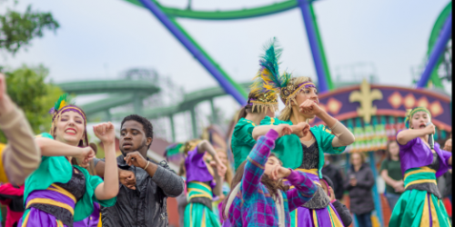 Group of Dancers and Guests dancing together with their arms in the air on the midway of the park