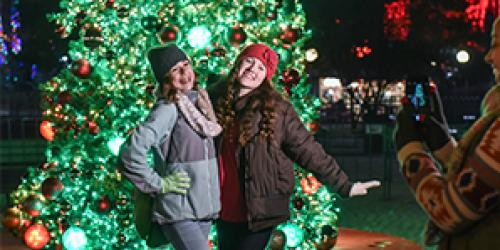 two girls taking a picture in front of an evergreen tree