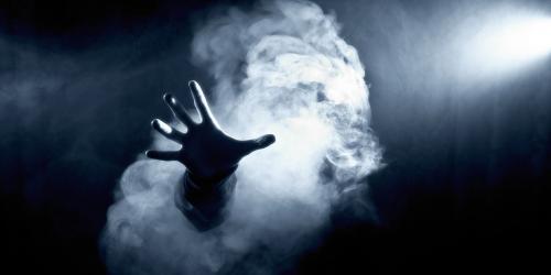 Hand through smoke in the dark