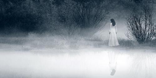 Woman in white dress walking along foggy lakeshore