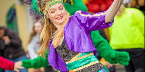 Performer dancing at the Mardi Gras festival with colorful clothing