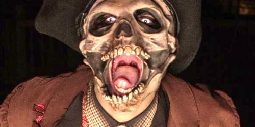 Actor in skull mask and western costume screaming at the camera