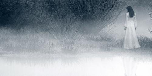 Woman in white dress walking along foggy lake shore