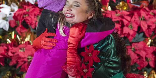 Poinsettia Princess hugging a girl